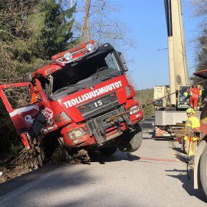 En bärgningsbil lyfter upp en lastbil ur ett dike.