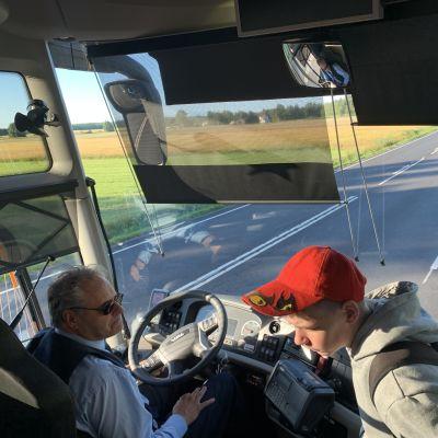 En elev kliver på bussen och går förbi chauffören på väg in.