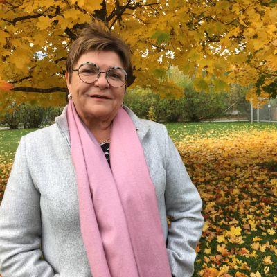Maria Tolppanen hymyilee kameralle. Taustalla on syksyisiä puita keltaisine lehtineen.