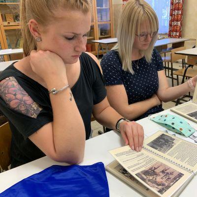 Kaksi tyttöä tutustuu koulumuseon luokkahuoneessa DDR:n aikaisiin koulukirjoihin.