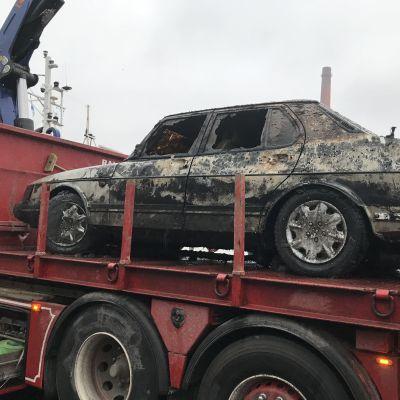 En rostig Saab 900, som lyfts upp ur Aura å, står på ett lastbilsflak.
