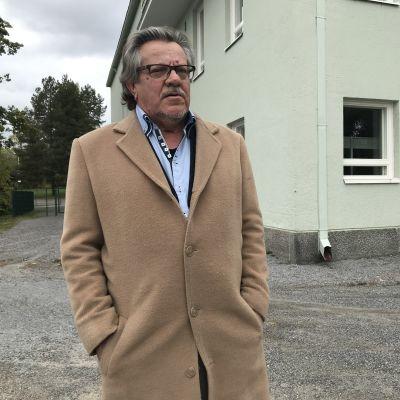 Hämeenkyrön Koskilinnan uusi omistaja, Rauno Hakala, seisoo rakennuksen edessä.