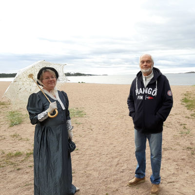 Bild på Tarja Kvarnström klädd i 1800-tals sommar kläder och Yrjö Sahlstedt på Belleveu stranden i Hangö.