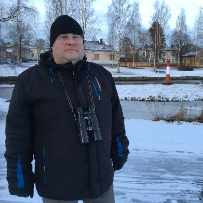 Mies seisoo talvimaisemassa kiikarit kaulassa, takana kaupunkimaisemaa.