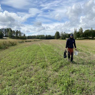 Emil Hästbacka tar jordprover från åkrar i Raseborg.