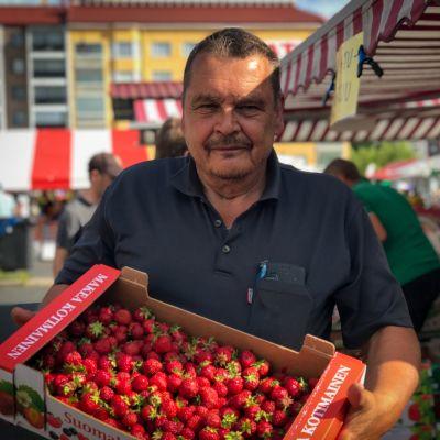 Mansikoita myyvä Matti Valtakivi esittelee mansikkalaatikkoa.