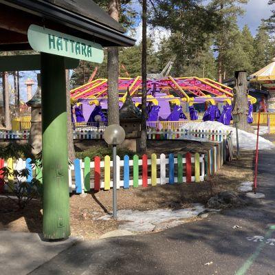 Huvipuistolaitteita autiossa huvipuistomaisemassa. Hattara-kyltti.