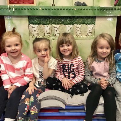 Fem glada barn i dagisåldern framför en grön kakelugn.