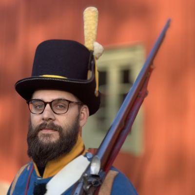 En man i historisk soldatuniform står med hatt på huvudet och geväret mot axeln.