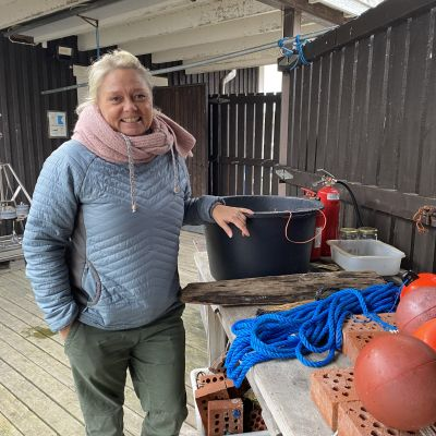 Ilse Klockars står vid ett bord med en hink och bojar.