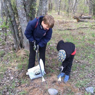 wilhelmina vitikainen och onni vitikainen plockar upp skräp i skogen runt runsala folkpark