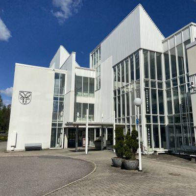 Kuvassa Tammelan kunnantalo ja kirjasto jotka sijaitsevat samassa rakennuksessa. Sisältä löytyy myös kahvio. Valkoinen rakennus hohtaa auringossa.