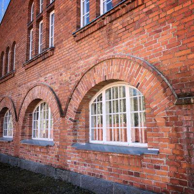 Punatiilinen rakennus, jossa isot ovet on korvattu ikkunoilla.