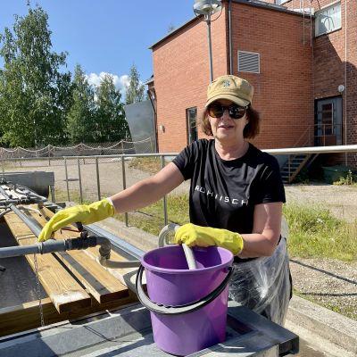Kajaanilainen Päivi Lappalainen pesemässä mattoja Kajaaninjoen rannalla.