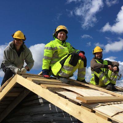 Kolme opiskelijaa työvaatteissa tekemässä pärekattoa venevajan katolla. Aurinkoinen sinitaivas taustalla.