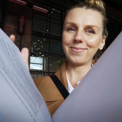 Hanna Gullichsen kauppakirjojen takana.