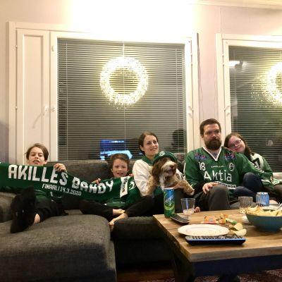 En familj med mamma, pappa och tre barn sitter i en soffa med en hund. De har gröna mössor och halsdukar på sig.