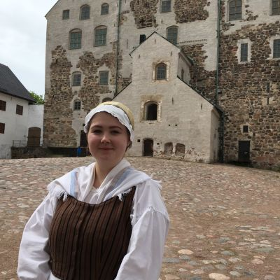 Guiden Cecilia Gustafsson står på Åbo slotts borggård, slottet syns i bakgrunden.