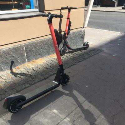 Två orange elsparkcyklar står i ett gathörnö.