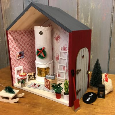 En liten låda formad som ett hus inredd till ett litet tomtebo