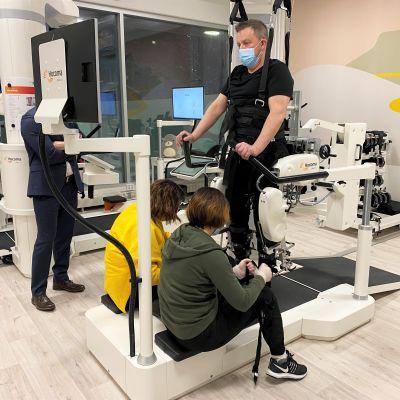 Premius kuntoutuksen fysioterapeutit Heidi Haromo ja Hanna Hellman auttavat Aarne Väänästä kävelyrobottiin Premiuksen tiloissa Kalevassa.