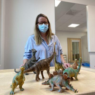 En kvinna är hukad vid ett bord med plastdinosaurier. Hon ser glad ut.