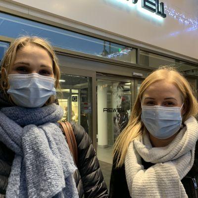 Två kvinnor med munskydd står utanför ingång till köpcentrum.