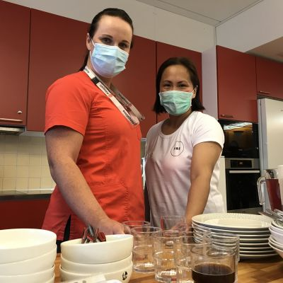 Kaksi hoitajaa maskit kasvoilla astioiden takana.