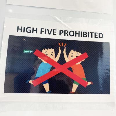 "En affisch på en vägg med texten ""high five prohibited""."