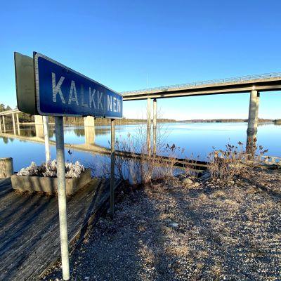 Kalkkisen kylän kyltti Kymijoen rannalla kirkkaana kevätaamuna kuvattuna.