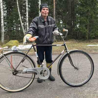 Håkan Weckström vid sin cykel, skog i bakgrunden.