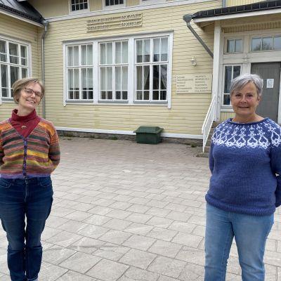 Två kvinnor framför ett gult gammalt trähus.