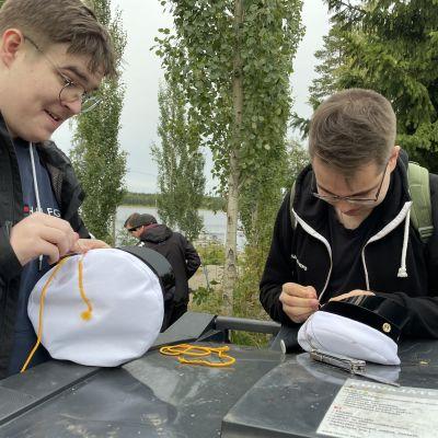 Kaksi poikaa koristelee ylioppilaslakkia luonnossa
