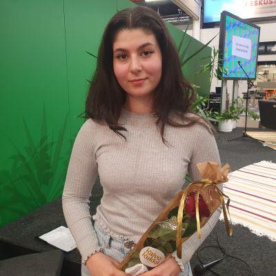 En ung kvinna med mörkt hår står inne i stor hall. Helsingfors bokmässa. Hon har en blomma och papperspåse (med present) i sina händer.