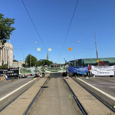 Demonstranter står med plakat på Mannerheimgatan vid riksdagshuset