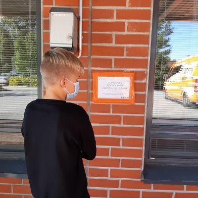 Nuori poika kasvomaskissa terveysaseman ovella menossa koronatestaukseen