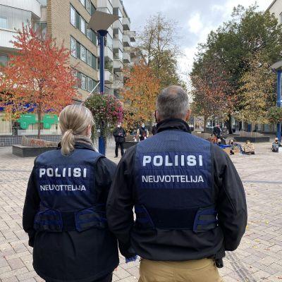 Kaksi poliisi katsoo kadulla istuvia mielenosoittajia Jyväskylässä Aren aukiolla.