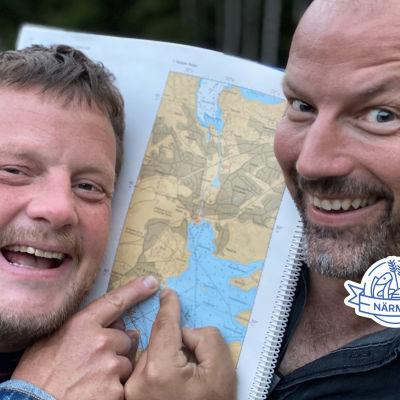 Micke och Matias pekar på en karta.