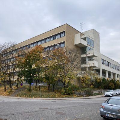 En gul och brun skolbyggnad i tegel i fyra våningar med höstgula träd omkring.