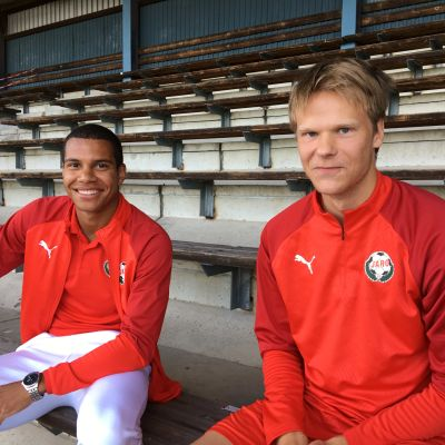 Kuvassa Anthony Olusanya ja Severi Kähkönen istuvat Pietarsaaren keskuskentän katsomossa.