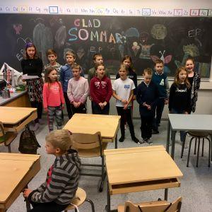 Salo svenska skola sjunger, läraren spelar piano.
