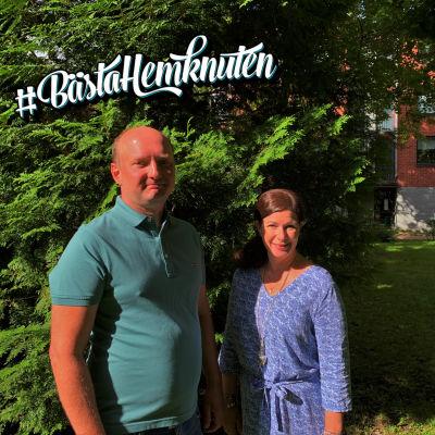 Sebastian Perret och Annika Roos står framför en grön buske, med ett rött tegelhus i bakgrunden, och ser in i kameran. Solen lyser i deras ansikten. Sebastian har inget hår, och en grön skjorta. Annika har långt, brunt hår och en blå klänning.