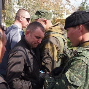 tunnuksettomat venäläissotilaat tarkistavat siviiliasuisten ukrainalaissotilaiden papereita Belbekin sotilastukikohdan portilla Krimillä