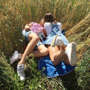 Nuoria suutelemassa viljapellossa, kuvassa myös Anna-Leena Härkösen kirja Häräntappoase
