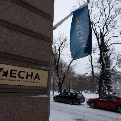 En skylt och en flagga med texten ECHA, utanför europeiska kemikaliemyndighetens fastighet på Annegatan i Helsingfors.