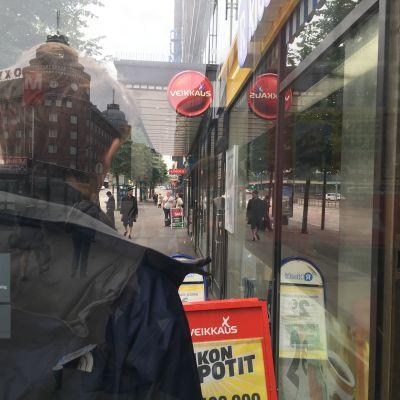 En man står utanför en R-kiosk och människor går på gatan omkring honom. Bilden är arrangerad.