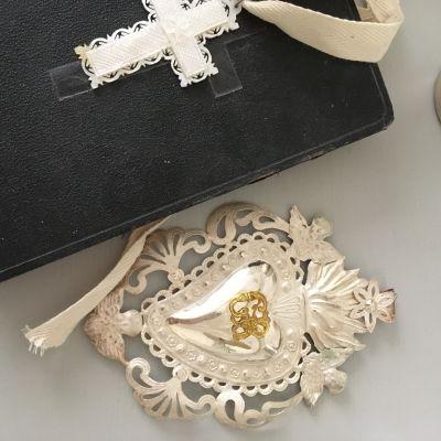En svart bibel med ett vitt pärlemorkors på och ett silverfärgat votiv.