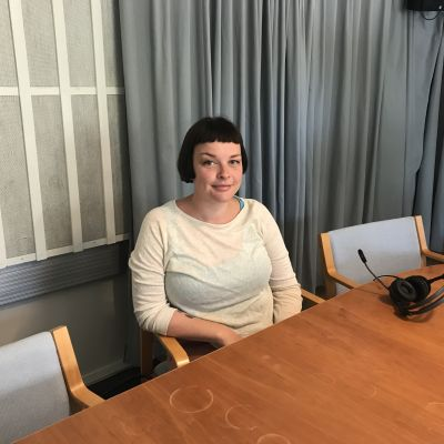 Sofia Enros sitter i en blå stol vid ett brunt kontorsbord. Hon har vit tröja och svart pagefrisyr.