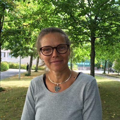 Kvinna med glasögon poserar vid träd