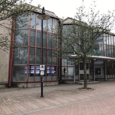 En kontorsbyggnad med roströda fönsterkarmar vid en gågata och ett par träd.